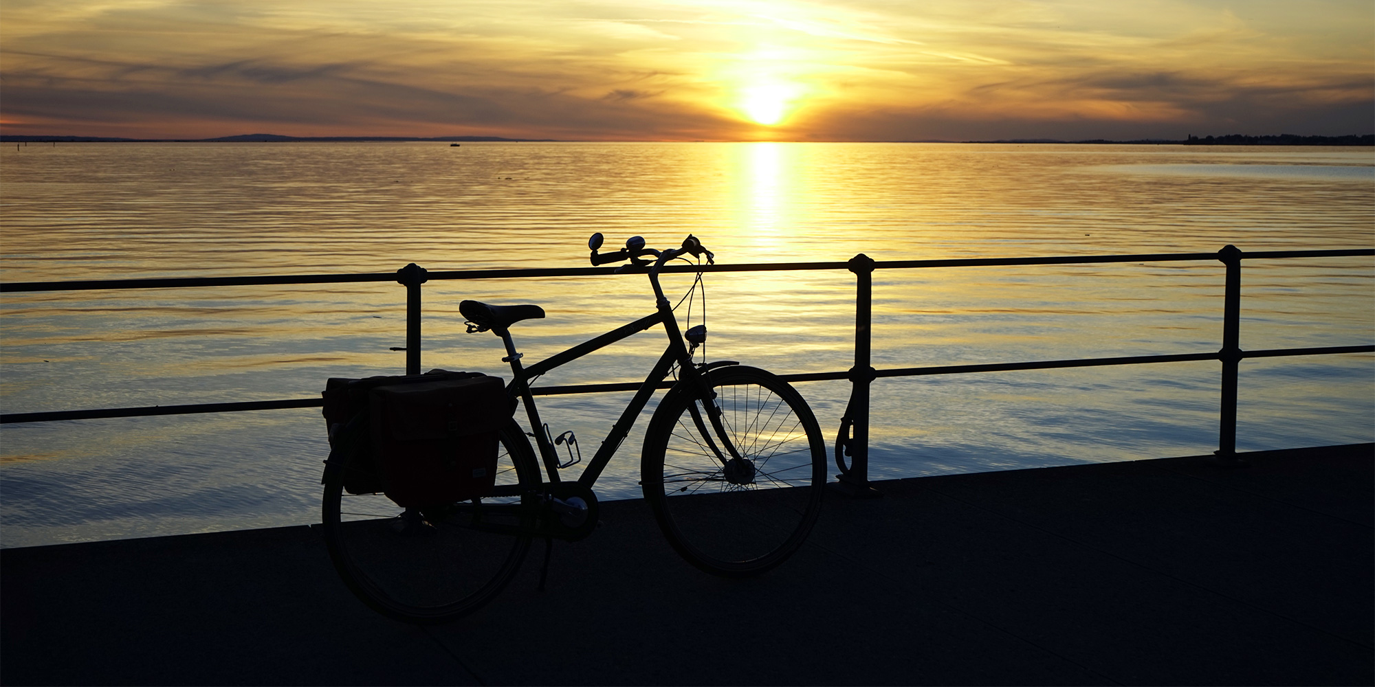 Silhouette of a bike on the beach at dusk.