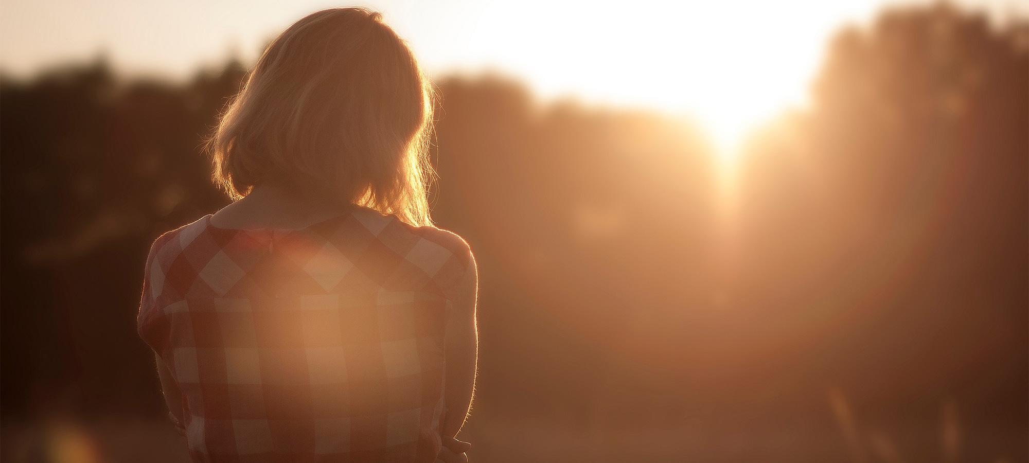 Women-overlooking the sunset at dusk